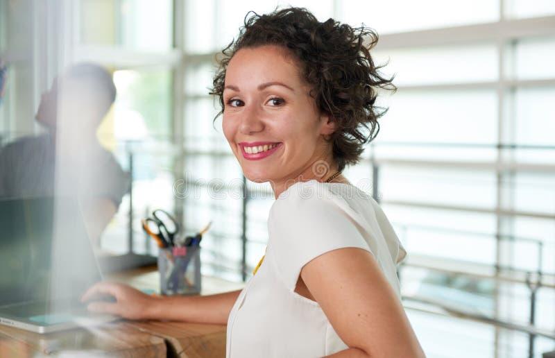 Beeld van een succesvolle toevallige bedrijfsvrouw die laptop met behulp van tijdens vergadering royalty-vrije stock foto's