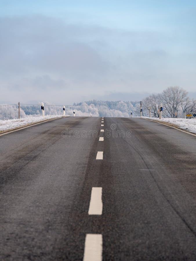 Beeld van een weg in een de winterlandschap stock afbeelding