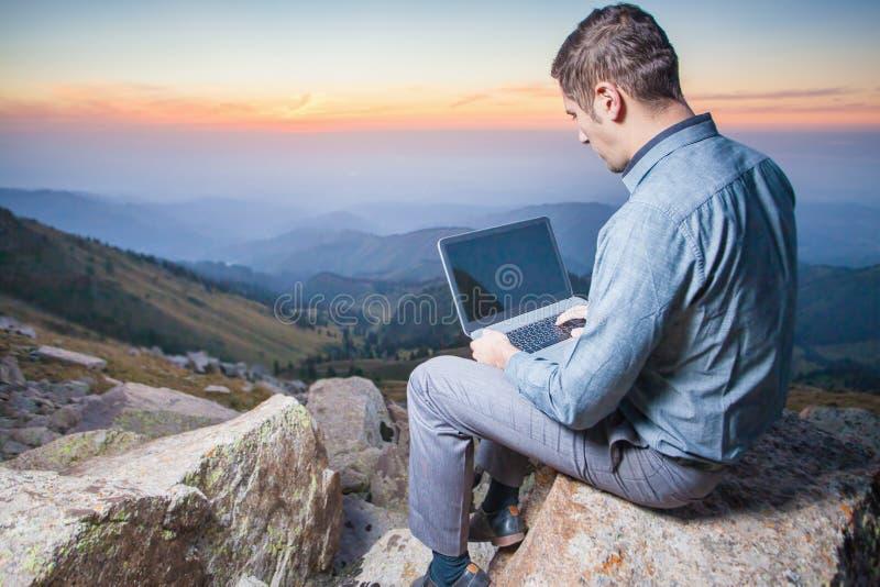 Beeld van een zakenman op de bovenkant van de berg, die laptop met behulp van stock afbeeldingen