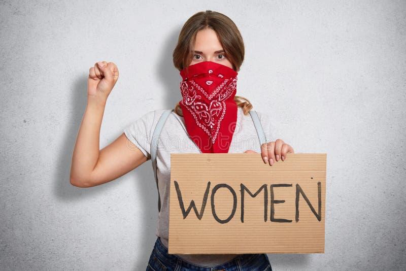 Beeld van ernstig bazig militant jong feministisch het opheffen wapen, die vuist tonen, houdend teken in één hand, die inschrijvi royalty-vrije stock foto's