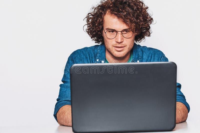 Beeld van ernstige Kaukasische zakenman die aan zijn laptop met krullend haar werken en toevallig blauw overhemd dragen stock foto