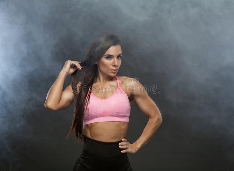 Beeld van fitness vrouw in sporten die zich in de rook kleden Jong vrouwelijk model met spierlichaam Horizontaal studioschot stock afbeeldingen
