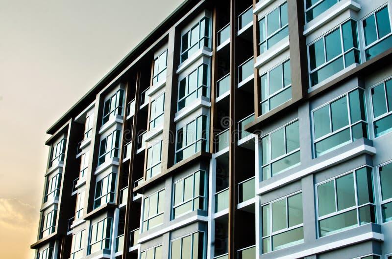 Beeld van flatgebouw met koopflats op middag met zonreeks stock fotografie