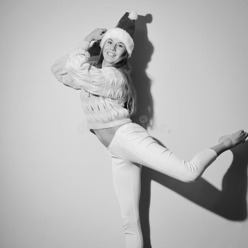 Beeld van gelukkig dansend meisje met Kerstmishoed stock fotografie