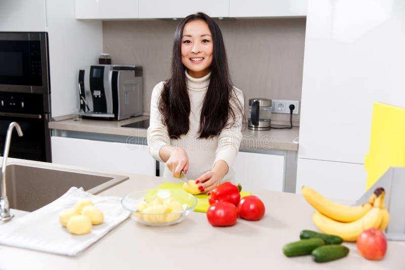 Beeld van gelukkige donkerbruine scherpe aardappels bij lijst met groenten en vruchten stock fotografie