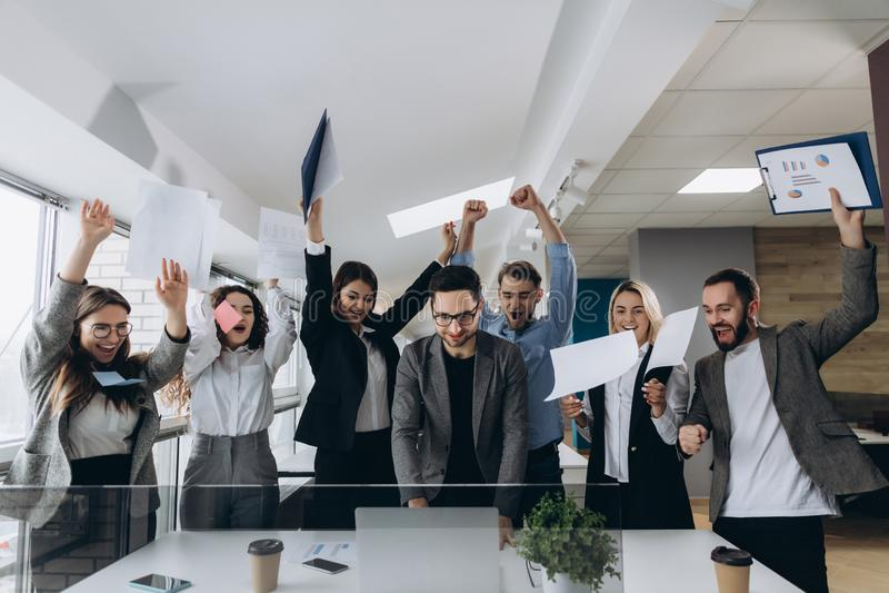 Beeld van gelukkige het commerciële team vieren overwinning in bureau Het succesvolle commerciële team werpt stukken van document stock foto