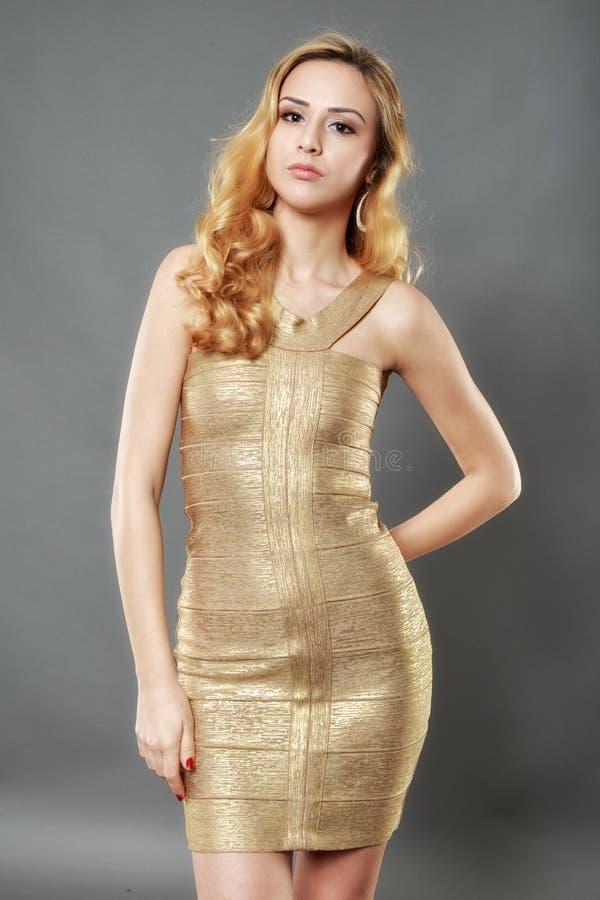 Beeld van gelukkige mooie jonge vrouw die het gouden kleding stellen dragen stock afbeeldingen