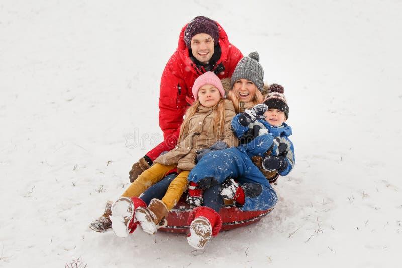 Beeld van gelukkige ouders met dochter en zoonszitting op buizenstelsel in de winter stock afbeeldingen