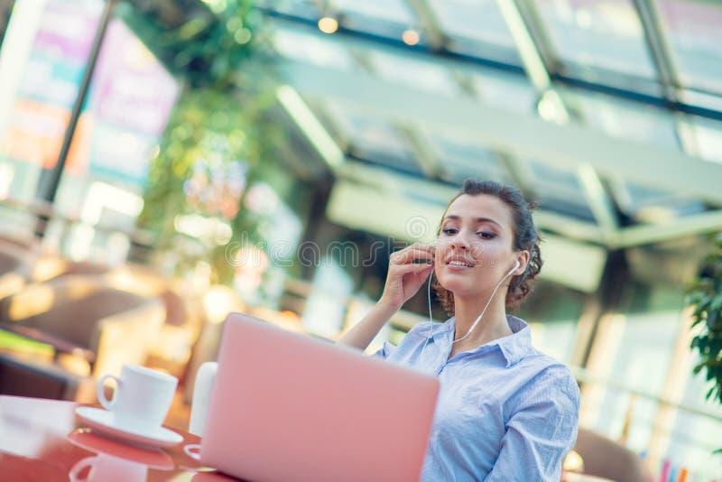 Beeld van gelukkige vrouw die laptop met behulp van terwijl het zitten bij koffie Jonge vrouwenzitting in een koffiewinkel en het stock afbeelding