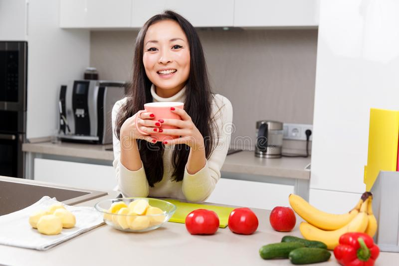Beeld van gelukkige vrouw met mok in handen die zich bij lijst met groenten en vruchten bevinden stock afbeeldingen