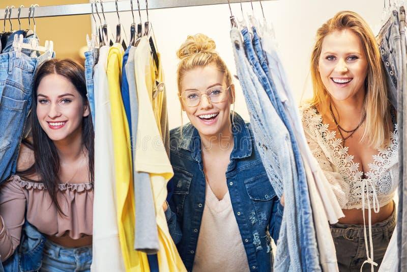 Beeld van groep gelukkige vrienden die voor kleren in wandelgalerij winkelen stock foto's