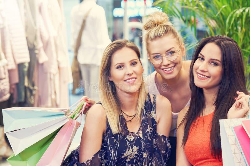 Beeld van groep gelukkige vrienden die voor kleren in wandelgalerij winkelen royalty-vrije stock foto's
