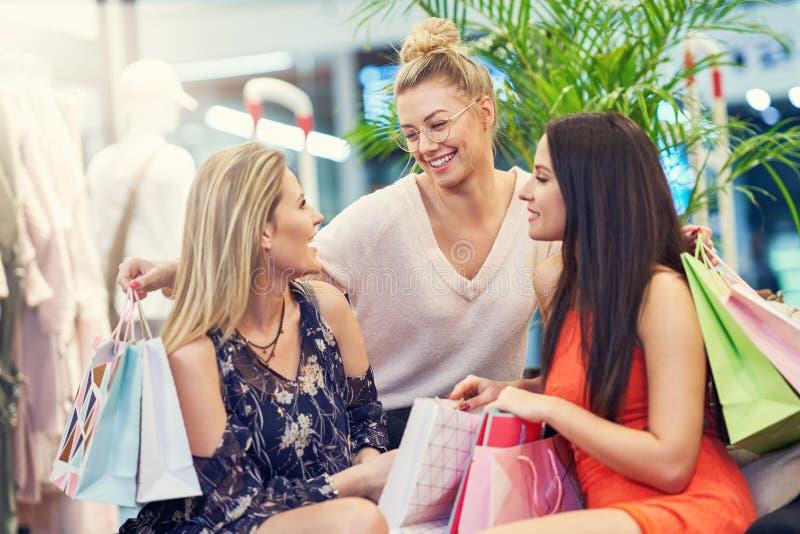 Beeld van groep gelukkige vrienden die voor kleren in wandelgalerij winkelen stock foto