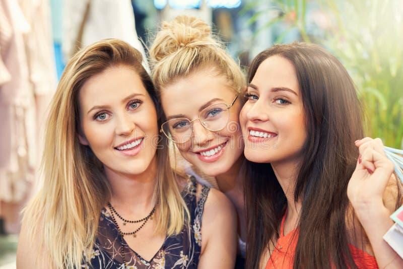 Beeld van groep gelukkige vrienden die voor kleren in wandelgalerij winkelen royalty-vrije stock fotografie