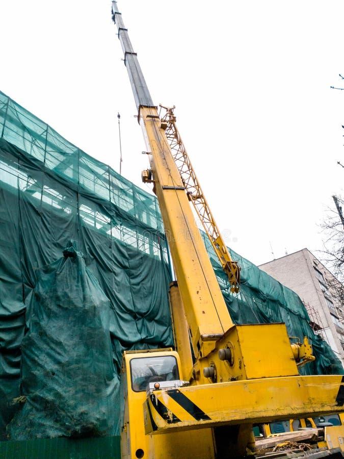 Beeld van grote mobiele kraan die aan bouwterrein werken royalty-vrije stock foto's