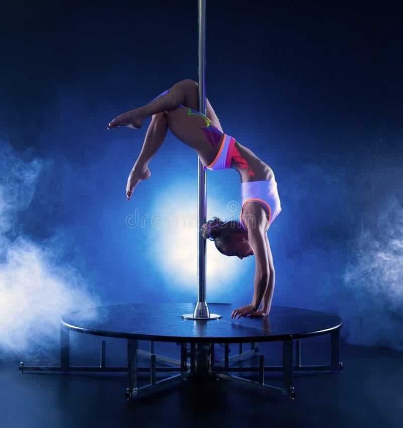 Beeld van het flexibele magere meisje dansen op pool stock foto's