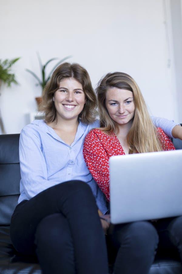 Beeld van het glimlachen twee jonge vrouwenzitting op de bank met laptop royalty-vrije stock afbeeldingen