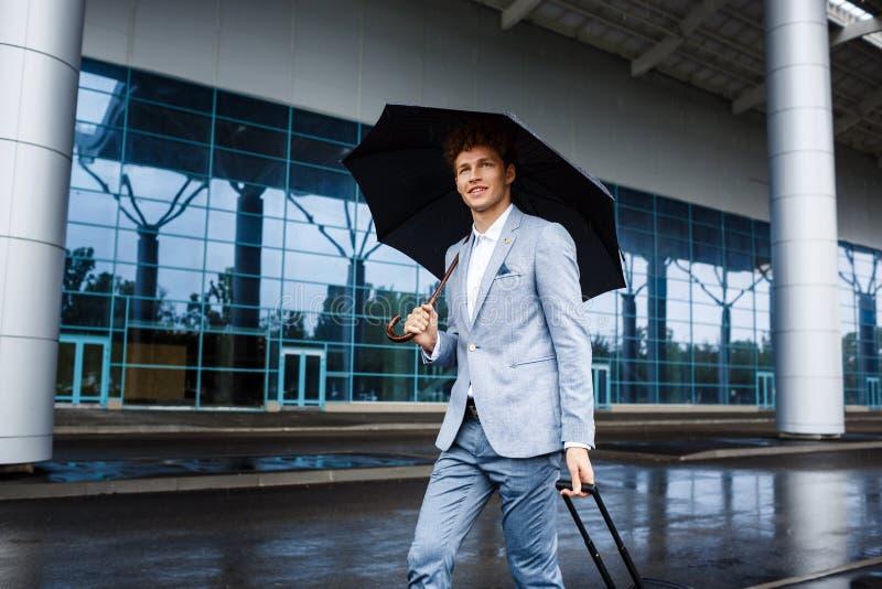 Beeld van het glimlachen van de jonge redhaired paraplu en de koffer van de zakenmanholding in regen bij luchthaven stock fotografie
