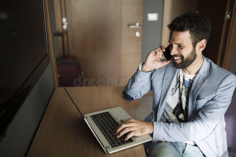 Beeld van het jonge succesvolle zakenman spreken op telefoon en het gebruiken van laptop stock afbeeldingen
