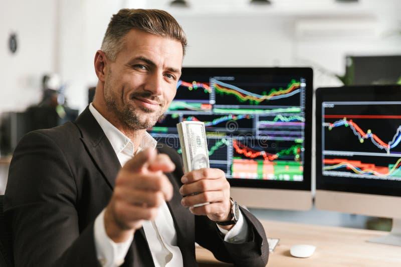 Beeld van het Kaukasische pak van de zakenmanholding van geld terwijl het werken in bureau met grafiek en grafieken aan computer royalty-vrije stock afbeelding