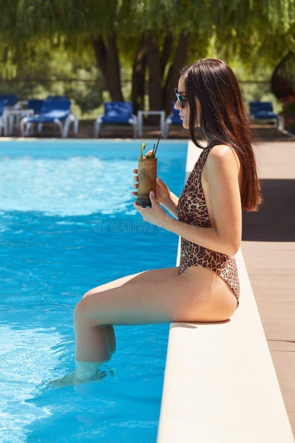 Beeld van het magnetische aantrekkelijke zoete jonge zwembad van de vrouwenzitting dichtbij, die goede alleen tijd hebben, het dr stock afbeeldingen