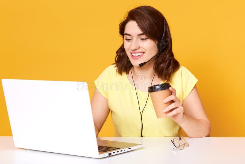 Beeld van het miling van het freelance exploitant werken online met hoofdtelefoons en laptop computer op kantoor of huis Vrolijk  stock foto