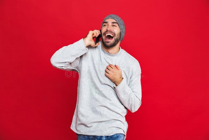 Beeld van het modieuze mens lachen terwijl het gebruiken van celtelefoon geïsoleerd over rode achtergrond stock foto