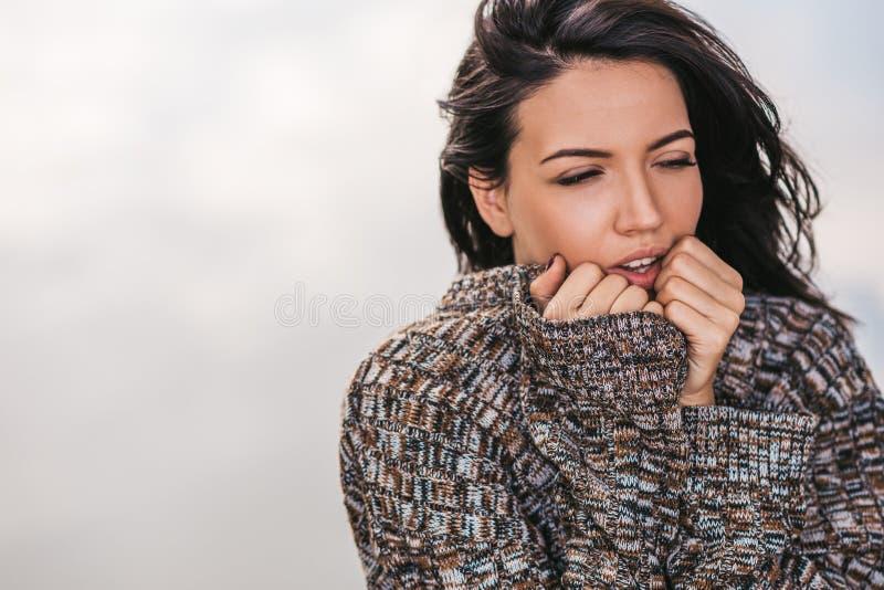 Beeld van het mooie droevige donkerbruine vrouwelijke stellen tegen meer met blazend haar Portret van het romantische vrouwelijke stock afbeelding