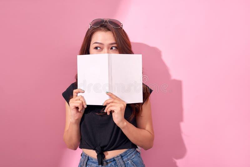 Beeld van het mooie jonge mooie vrouw stellen over roze het boeklezing van de achtergrondmuurholding royalty-vrije stock afbeeldingen