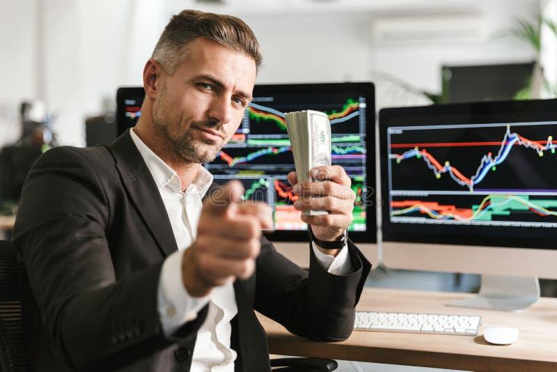 Beeld van het volwassen pak van de zakenmanholding van geld terwijl het werken in bureau met grafiek en grafieken aan computer stock afbeeldingen