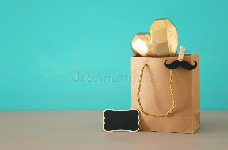 Beeld van het winkelen zak met gouden hart, heden voor papa Het Concept van de vader` s Dag stock fotografie