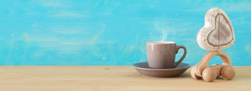 Beeld van hete koffie of thee naast stuk speelgoed auto met hart over houten lijst Het Concept van de vader` s Dag royalty-vrije stock foto's