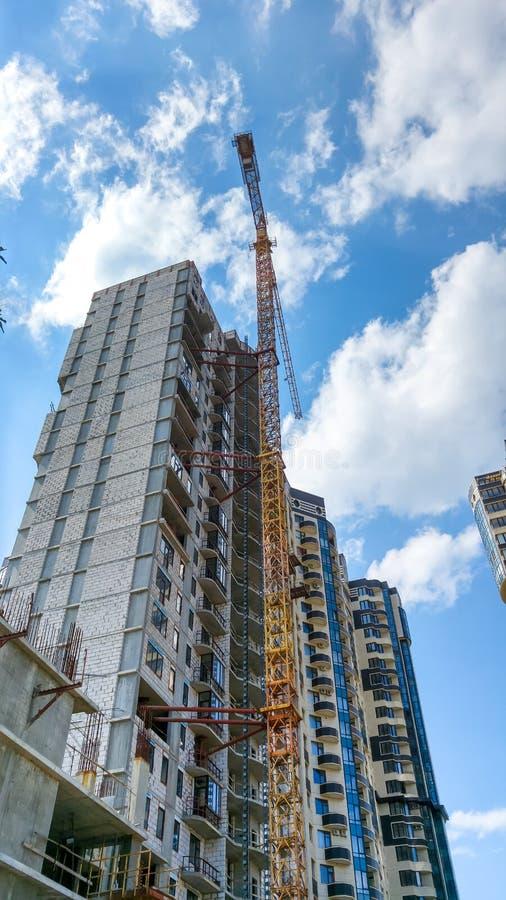 Beeld van hoge de bouwkraan op bouwwerf van nieuw modern district tegen blauwe hemel met witte wolken royalty-vrije stock afbeelding