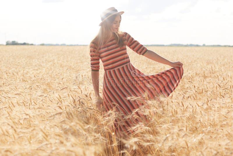 Beeld van jong mooi meisje die in modieuze gestreepte kleding en strohoed op tarwegebied lopen op zonnige de zomerdag, het geniet stock afbeeldingen