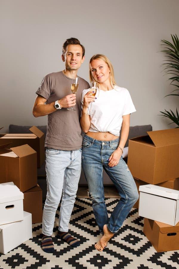 Beeld van jong paar met wijnglazen die zich onder kartondozen bevinden stock afbeelding
