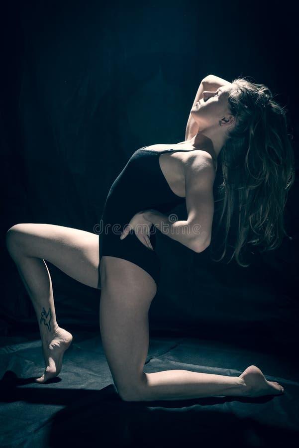 Beeld van jonge aantrekkelijke vrouw met geschikt lichaam in zwarte bodysuit die zich in een cirkel van licht op zwarte achtergro stock afbeelding