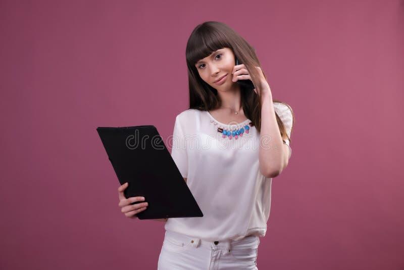 Beeld van jonge bedrijfsvrouw status over roze achtergrond die opzij babbelend door de omslag van de telefoonholding kijken royalty-vrije stock afbeeldingen