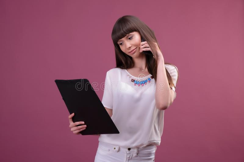 Beeld van jonge bedrijfsvrouw status over roze achtergrond die opzij babbelend door de omslag van de telefoonholding kijken royalty-vrije stock foto's