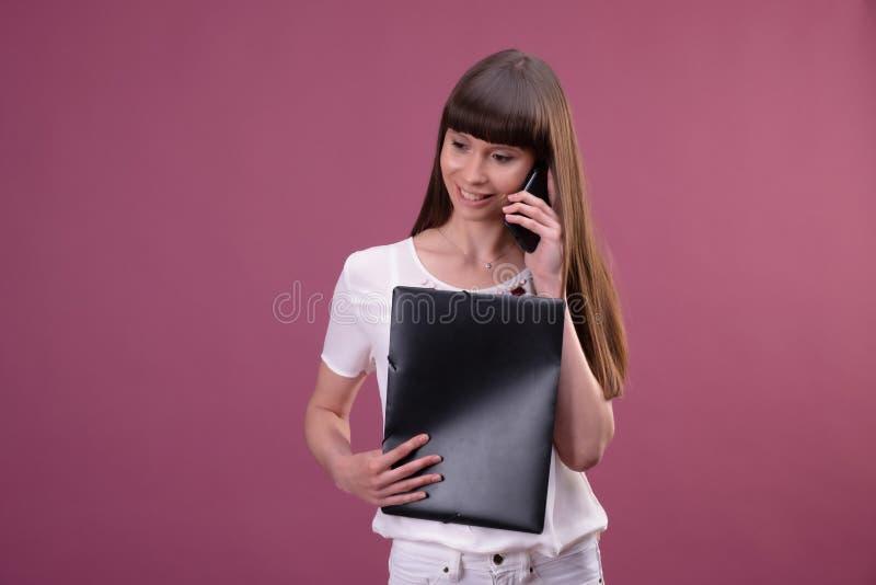 Beeld van jonge bedrijfsvrouw status over roze achtergrond die opzij babbelend door de omslag van de telefoonholding kijken royalty-vrije stock afbeelding