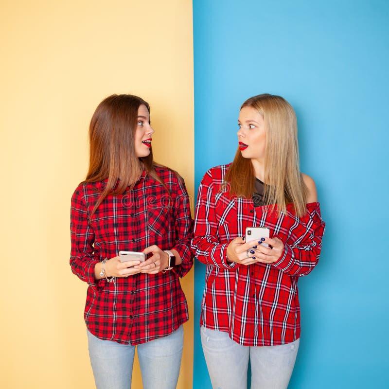 Beeld van jonge gelukkige vrouwenvrienden die zich over gele en blauwe muur bevinden stock afbeelding