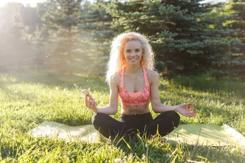 Beeld van jonge krullend-haired sportenvrouw het praktizeren yoga op deken in park royalty-vrije stock fotografie