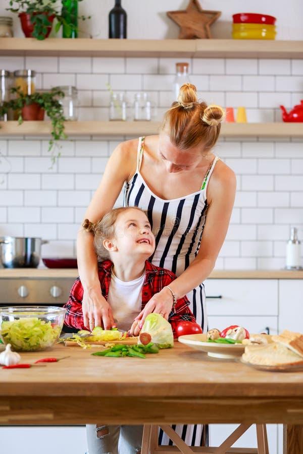 Beeld van jonge moeder met haar dochter kokend voedsel in keuken stock foto