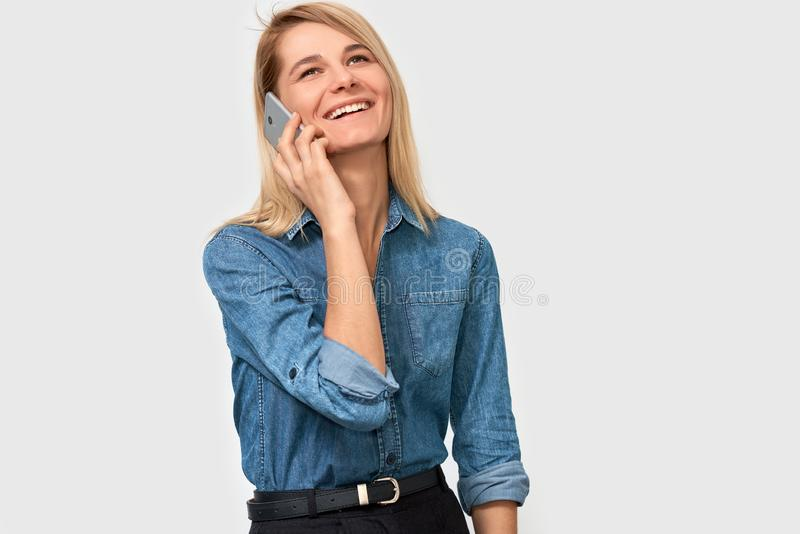 Beeld van jonge mooie blondevrouw in denimoverhemd die en op smartphone aan haar vriend glimlachen spreken, die vrolijk en gelukk stock foto's