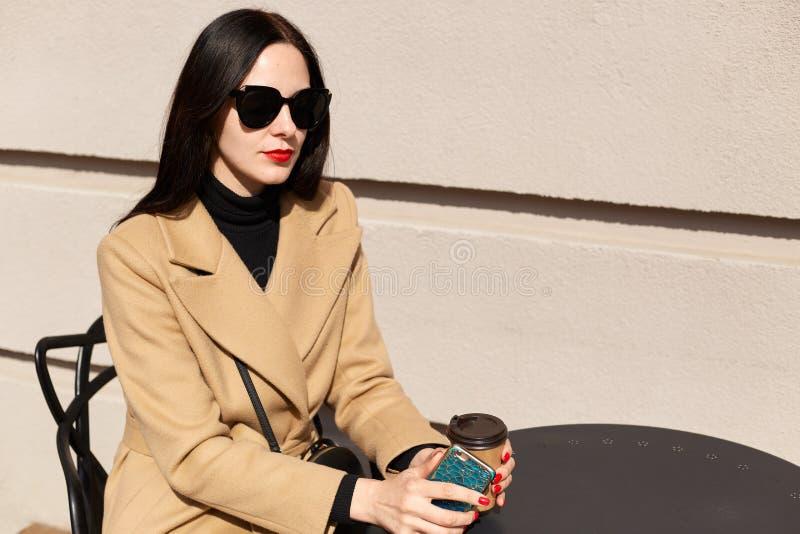 Beeld van jonge mooie donkerbruine vrouw in zwarte zonnebril en beige modieuze laagzitting bij lijst in openluchtkoffie, heet dri stock foto