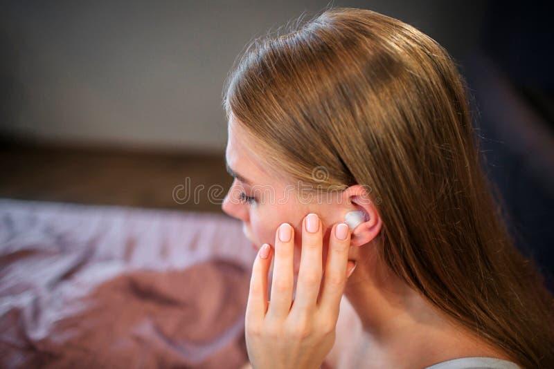Beeld van jonge vrouwenzitting op bed Zij houdt hand dicht bij oor Zij richt op het Het is gesloten met stuk van katoen royalty-vrije stock afbeelding