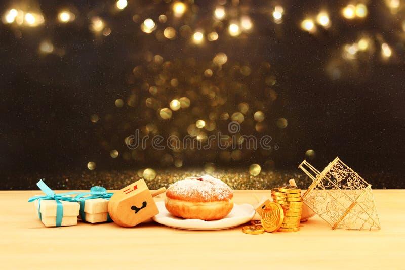 Beeld van Joodse vakantiechanoeka met houten dreidels & x28; het spinnen top& x29; en doughnut op de lijst stock fotografie