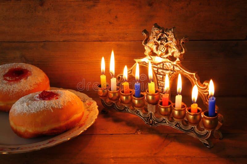 Beeld van Joodse vakantiechanoeka met menorah (traditionele Kandelabers), donuts en houten dreidels (tol) stock fotografie