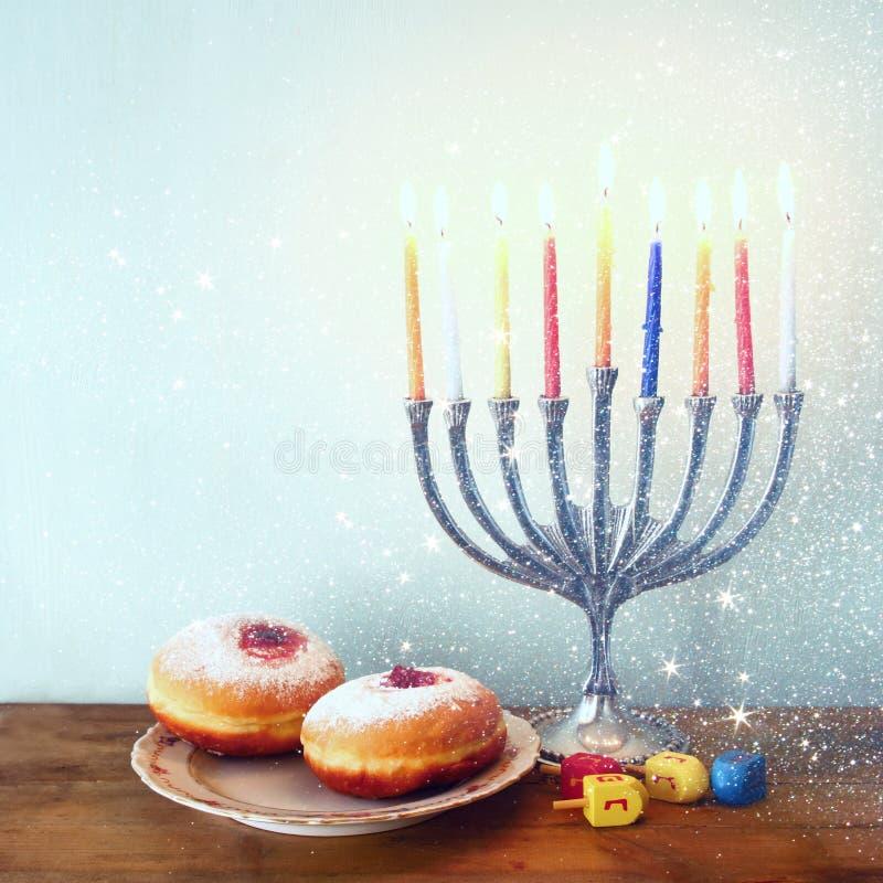 Beeld van Joodse vakantiechanoeka met menorah (traditionele Kandelabers), donuts en houten dreidels (tol) Gefiltreerd Retro stock afbeelding