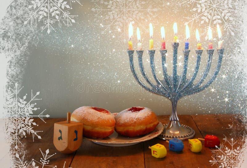 Beeld van Joodse vakantiechanoeka met menorah (traditionele Kandelabers), donuts en houten dreidels (tol) Gefiltreerd Retro stock afbeeldingen