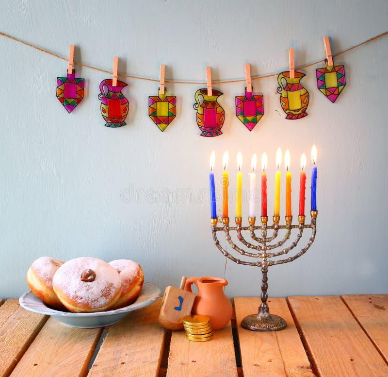 Beeld van Joodse vakantiechanoeka met menorah (traditionele Kandelabers), donuts en houten dreidels (tol) schitter backgro stock afbeeldingen